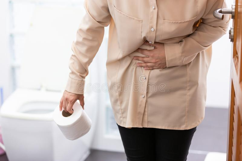 A mulher asiática sofre do rolo do tecido da terra arrendada da diarreia ou o papel higiênico perto de uma bacia de toalete, meni imagem de stock