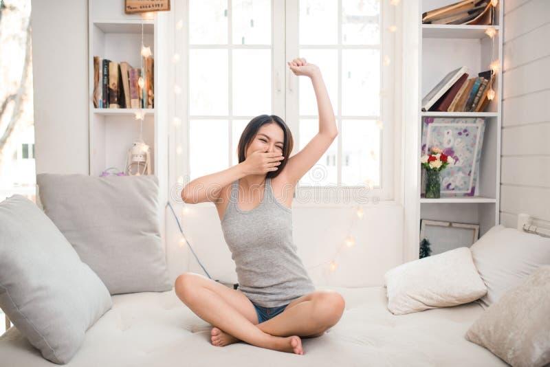 Mulher asiática sonolento cansado que acorda e que estica ao sentar-se fotografia de stock royalty free