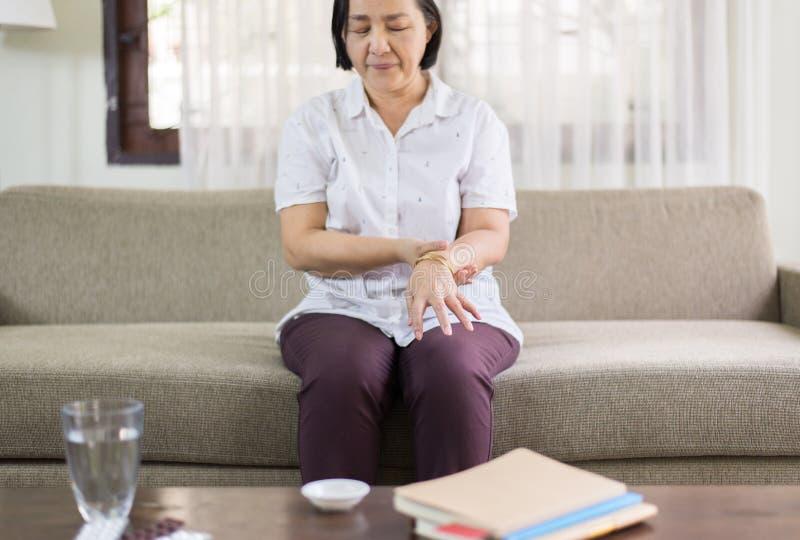 Mulher asiática superior que sofre com sintomas da doença de Parkinson nas mãos fotos de stock