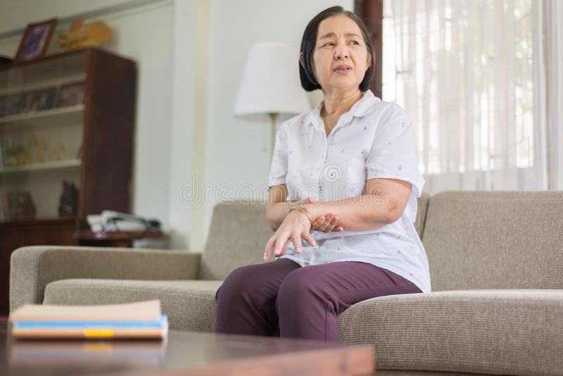 Mulher asiática superior que sofre com sintomas da doença de Parkinson nas mãos fotografia de stock royalty free