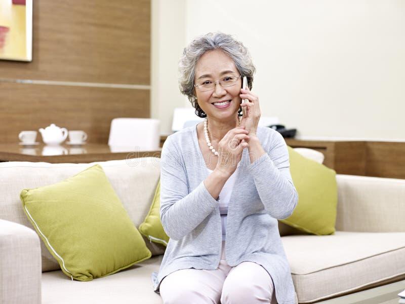 Mulher asiática superior que usa o telefone celular imagem de stock royalty free