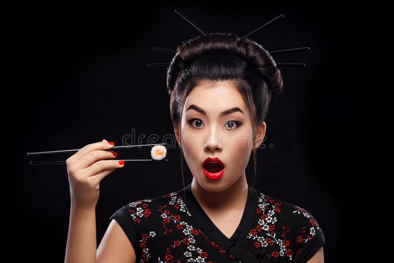 Mulher asiática surpreendida que come o sushi e os rolos em um fundo preto fotografia de stock