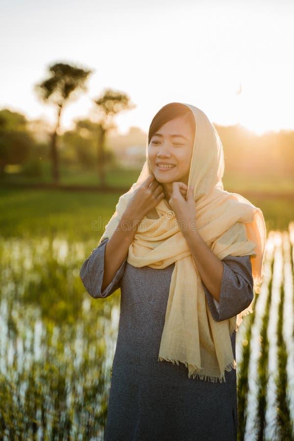 A mulher asiática tenta fixar seu lenço principal imagens de stock royalty free