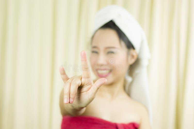 A mulher asi?tica veste uma saia para cobrir seu peito ap?s o cabelo da lavagem, envolvido nas toalhas ap?s o chuveiro e a doa??o foto de stock