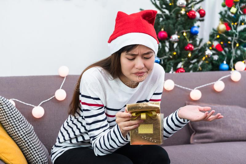 Mulher asiática virada quando caixa de presente aberta do xmas do ouro na festa natalícia no sofá, presente da festa de Natal do  fotos de stock royalty free