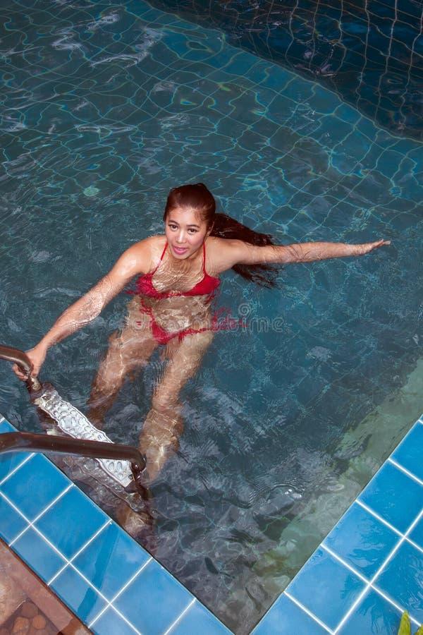 Mulher asi?tica bonita que veste a nadada vermelha do biquini e que est? na escada na piscina fotografia de stock