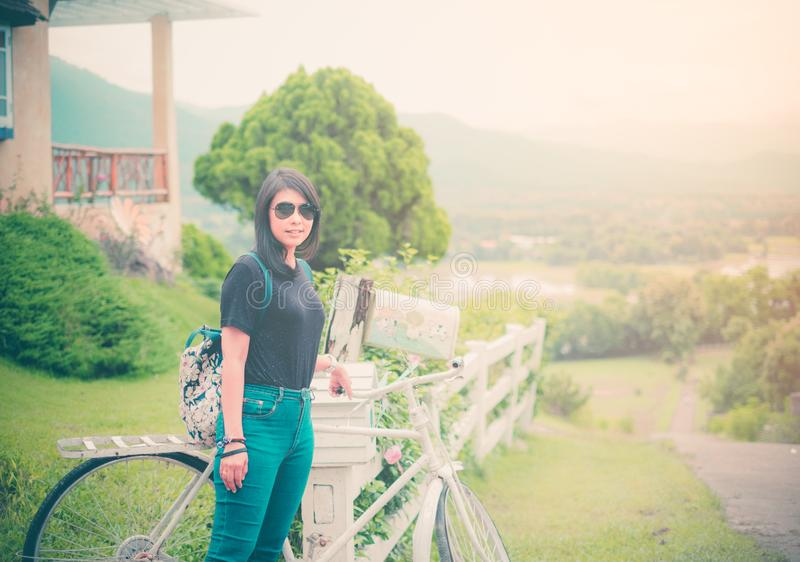 Mulher asi?tica bonita Vista um t-shirt do preto do vestido ocasional com calças de brim verdes backpack Estando com uma biciclet imagens de stock royalty free