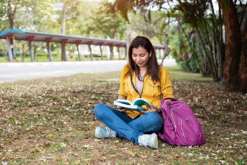 Mulher asi?tica feliz que senta-se e livros de leitura no parque da universidade sob a ?rvore grande Estilos de vida dos povos e  fotos de stock royalty free