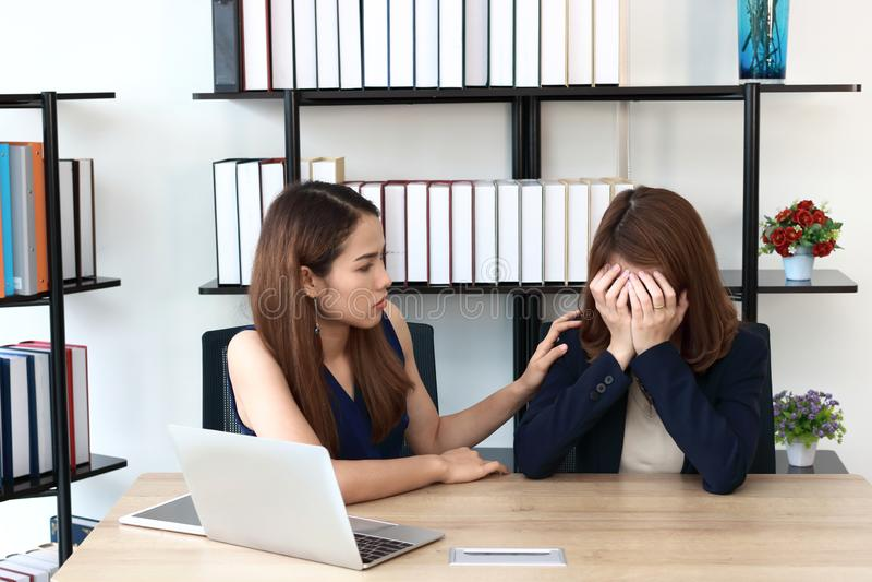 Mulher asi?tica nova que consola seus colegas deprimidos tristes no escrit?rio foto de stock