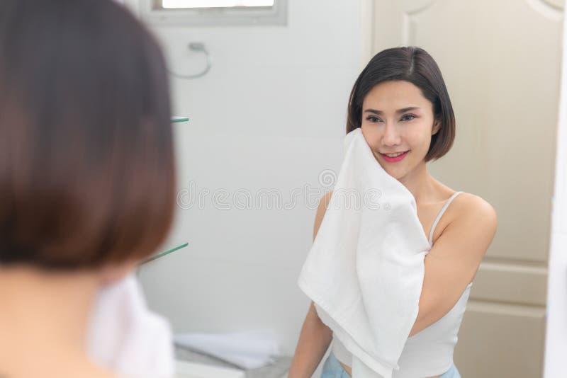Mulher asi?tica nova que limpa sua cara com a toalha no banheiro imagens de stock