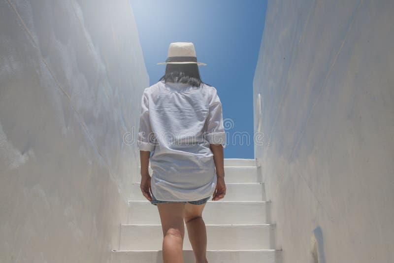 Mulher asi?tica para vestir a camisa branca e para tecer o chap?u que anda acima em escadas concretas imagens de stock royalty free