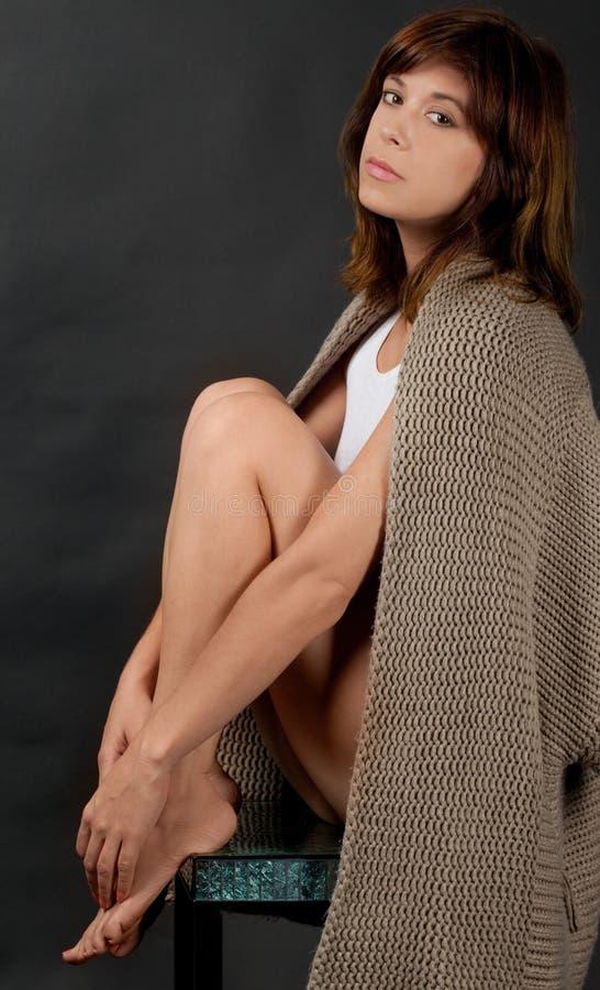 Mulher assentada com a camiseta drapejada sobre ombros fotografia de stock royalty free