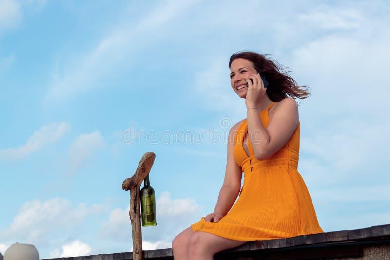 Mulher assentada em um cais em um lugar tropical usando seus smartphone e sorriso C?u com as nuvens como o fundo fotos de stock