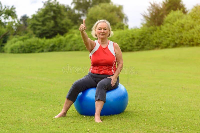 Mulher assentada na bola da estabilidade com polegar acima foto de stock