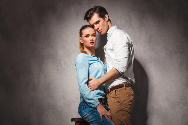 A mulher assentada ocasional nova é abraçada por seu noivo imagem de stock