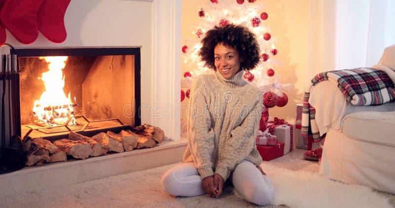 Mulher assentada pela árvore e pelos presentes do White Christmas fotografia de stock
