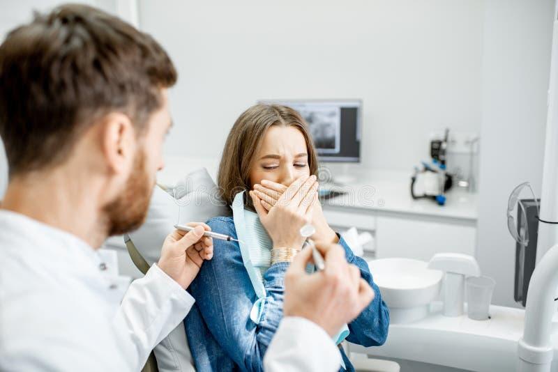 Mulher assustado durante o procedimento no escritório dental imagens de stock