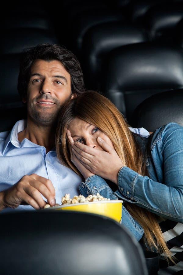 Mulher assustado que inclina-se no homem no teatro do cinema imagem de stock