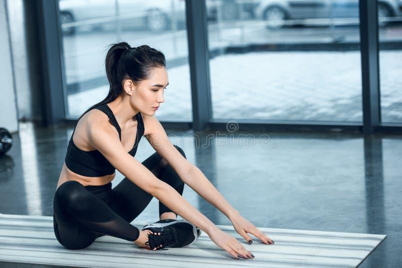 mulher athhletic nova que estica na esteira da ioga imagens de stock royalty free
