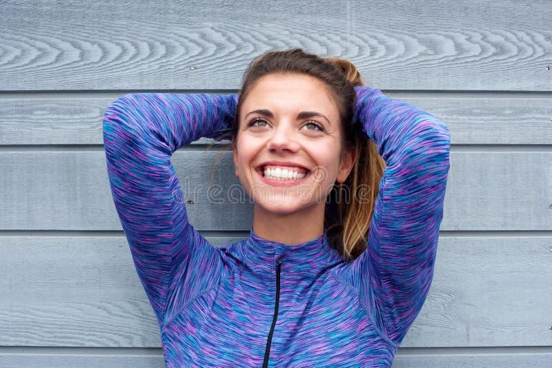 Mulher ativa de sorriso que está com mãos atrás da cabeça fotos de stock