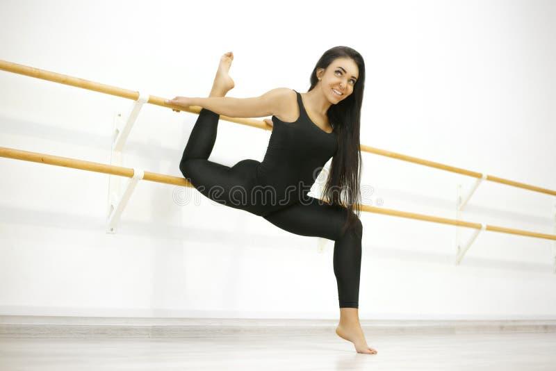 A mulher ativa nova em um t-shirt e em caneleiras, executa exerc?cios do estic?o e da ioga em um est?dio moderno fotos de stock