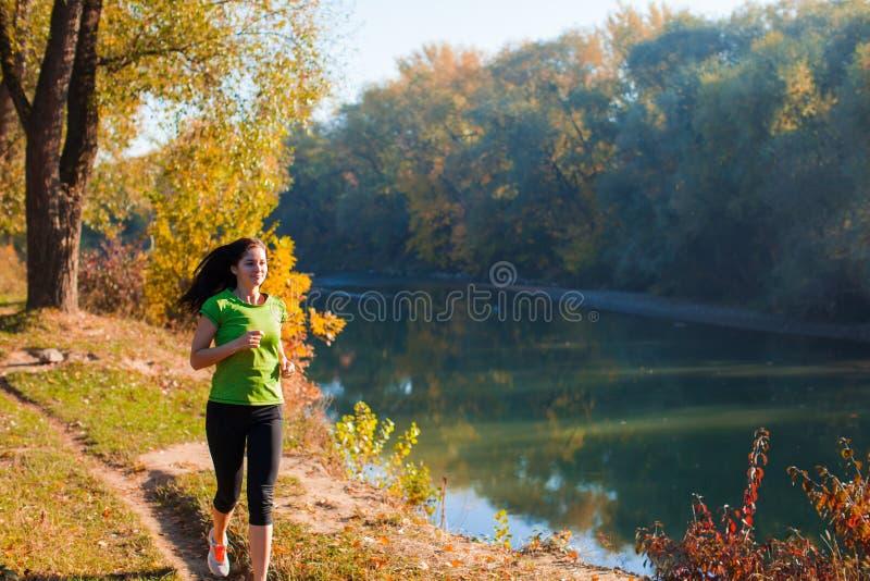 Mulher ativa nova que movimenta-se ao longo do rio fotografia de stock royalty free