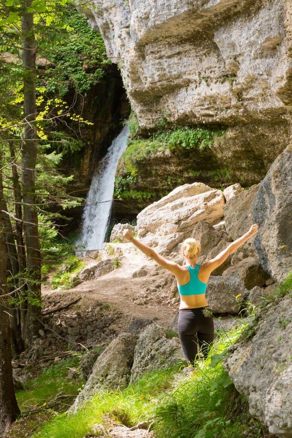 Mulher ativa que aumenta os bra?os que inalam o ar fresco, sentindo relaxado na natureza imagem de stock royalty free