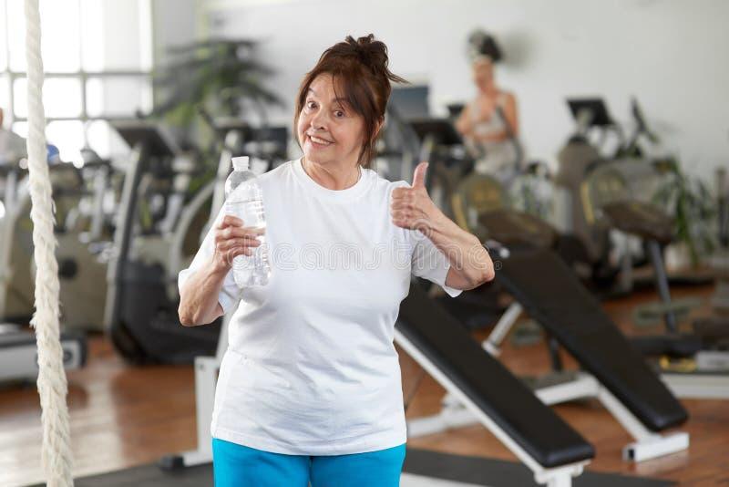 Mulher ativa que dá o polegar acima no gym fotografia de stock