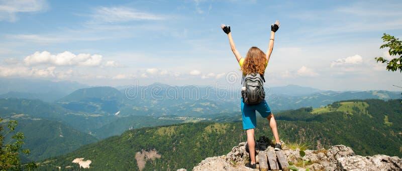 Mulher ativa que gesticula o sucesso após ter escalado uma montanha imagem de stock