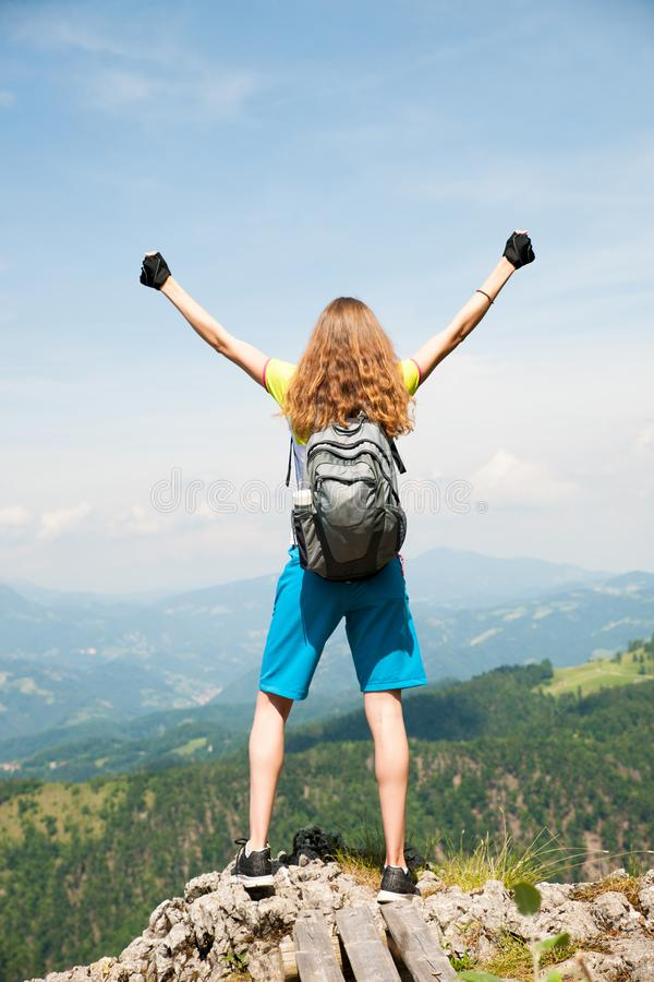 Mulher ativa que gesticula o sucesso após ter escalado uma montanha fotografia de stock royalty free