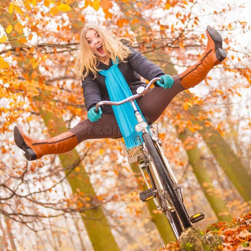 Mulher ativa que tem a bicicleta da equitação do divertimento no parque do outono foto de stock