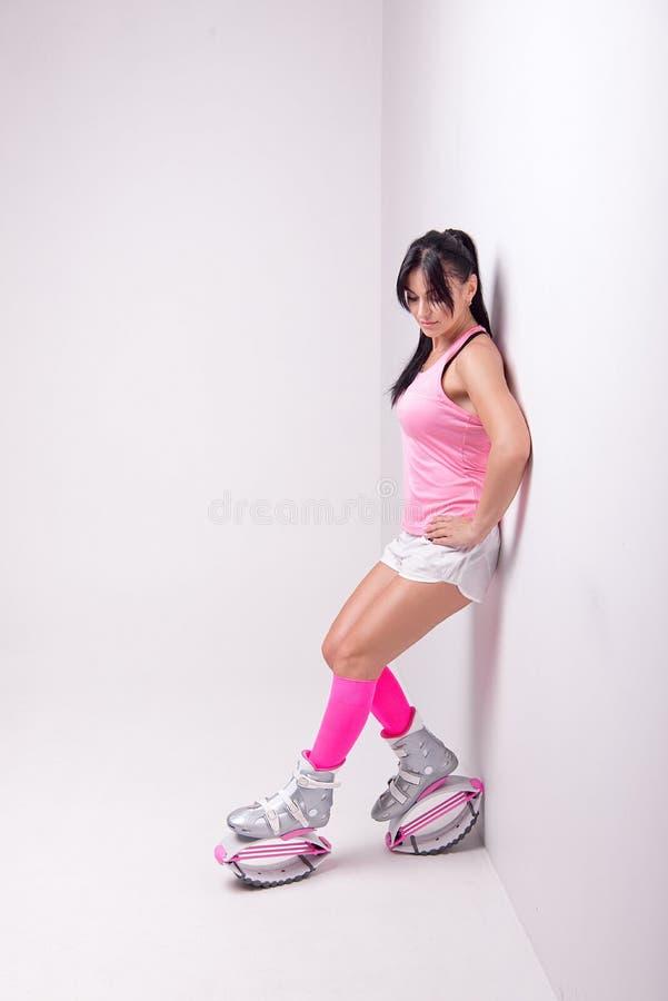 A mulher atlética bonita que veste na roupa do estilo dos esportes com as botas dos saltos do kangoo em seus pés faz exercis dos  imagem de stock