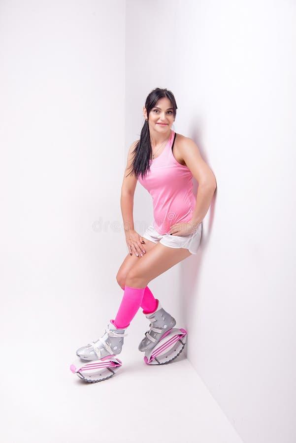 A mulher atlética bonita que veste na roupa do estilo dos esportes com as botas dos saltos do kangoo em seus pés faz exercis dos  foto de stock