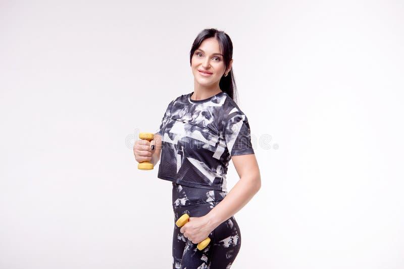 A mulher atlética bonita que veste na roupa do estilo dos esportes faz exercis dos esportes imagem de stock royalty free