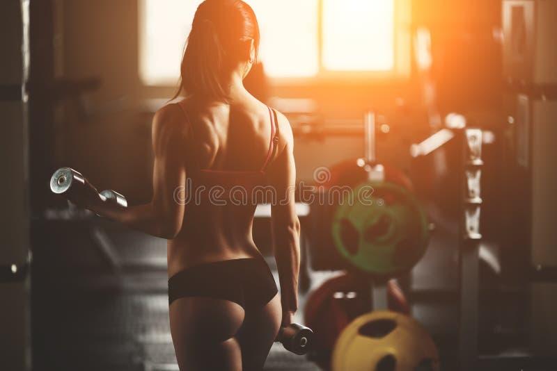 A mulher atlética brutal que bombeia acima muscles com fotografia de stock