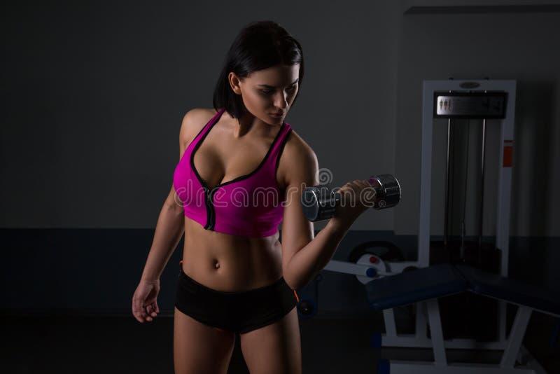 A mulher atlética brutal que bombeia acima muscles com pesos fotos de stock