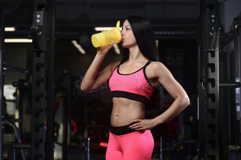Mulher atlética considerável da aptidão que guarda um abanador e um levantamento fotos de stock royalty free