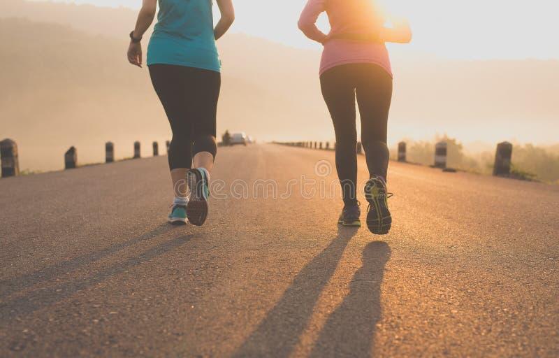 Mulher atlética dos pares que movimenta-se e que corre fora na estrada na manhã foto de stock royalty free