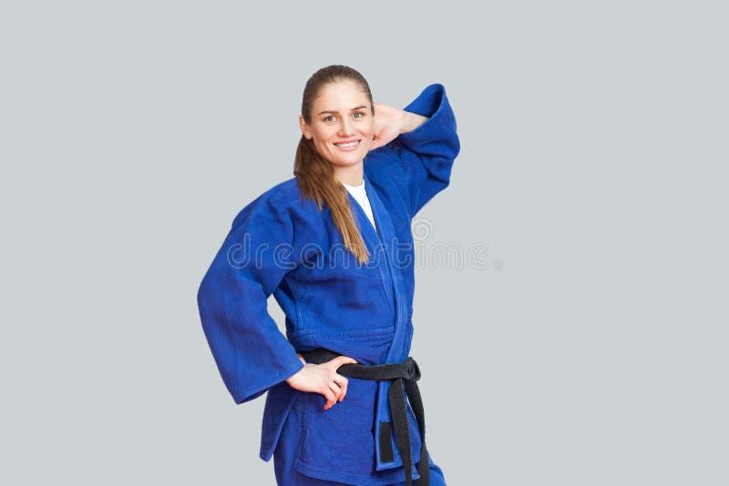 Mulher atlética feliz bonita do karaté no quimono azul com preto imagem de stock royalty free