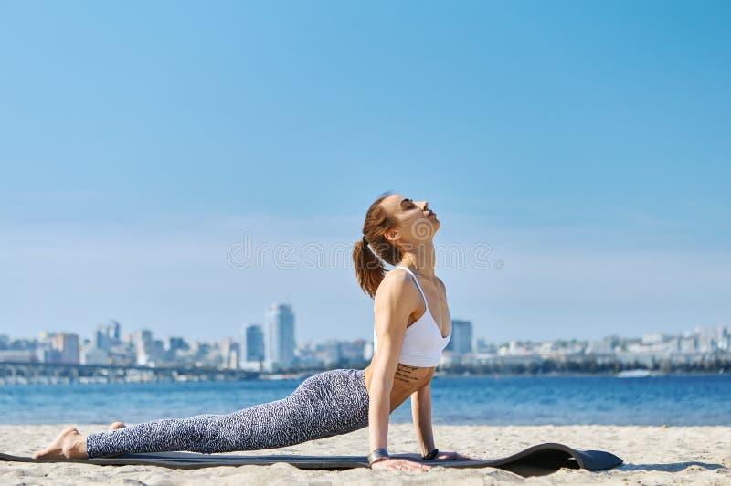 A mulher atlética magro nova faz exercícios da ioga e esticão na praia da areia com fundo da cidade Estilo de vida saud?vel foto de stock