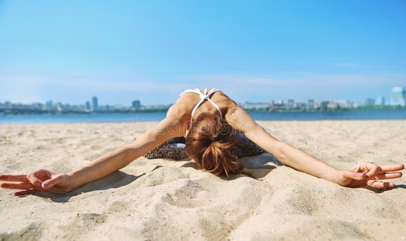 A mulher atlética magro nova faz exercícios da ioga e esticão na praia da areia com fundo da cidade Estilo de vida saud?vel imagem de stock royalty free