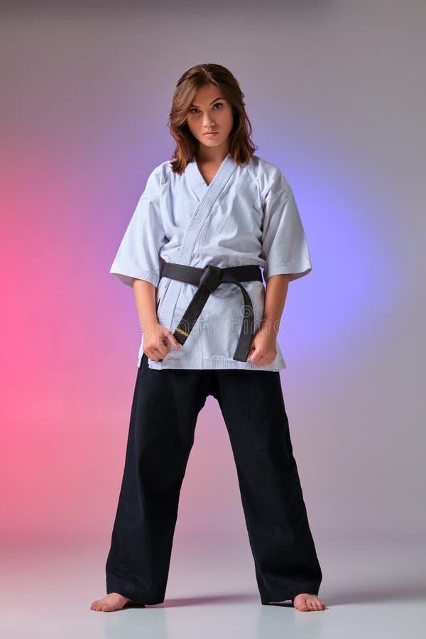 A mulher atlética no quimono tradicional está praticando o karaté no estúdio fotos de stock royalty free