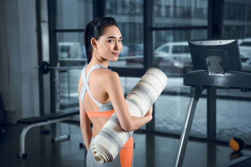 mulher atlética nova com a esteira rolada da ioga fotografia de stock