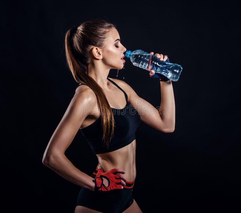 Mulher atlética nova na água potável do sportswear no estúdio contra o fundo preto Figura fêmea ideal dos esportes fotografia de stock royalty free