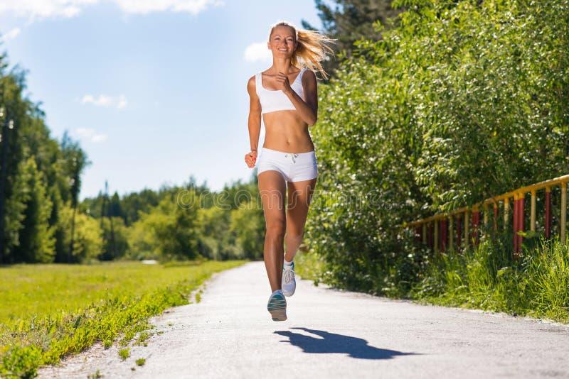 Mulher atlética nova que corre na estrada imagens de stock