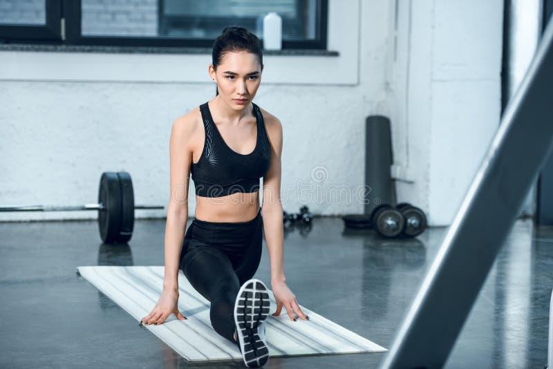 mulher atlética nova que estica o pé na esteira da ioga fotos de stock