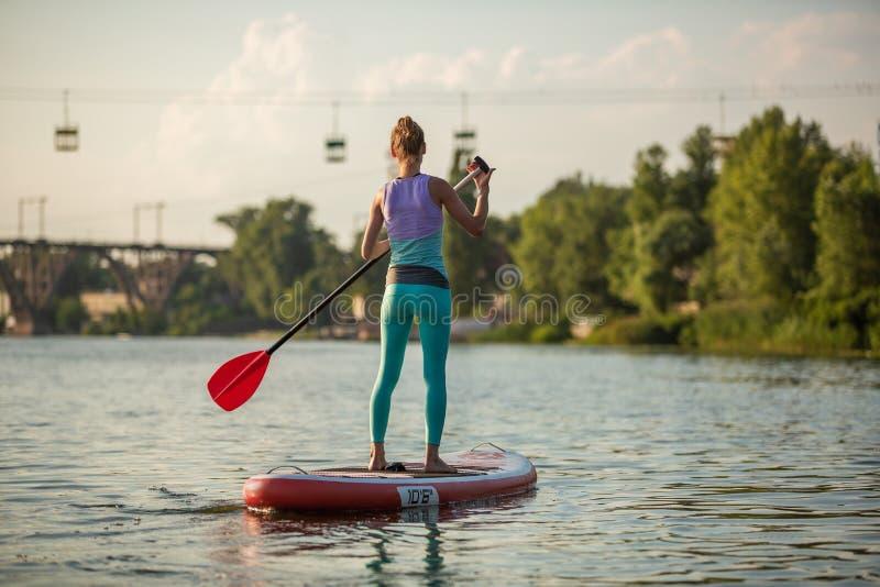 Mulher atlética nova que faz a aptidão em uma placa com um remo em um lago imagens de stock