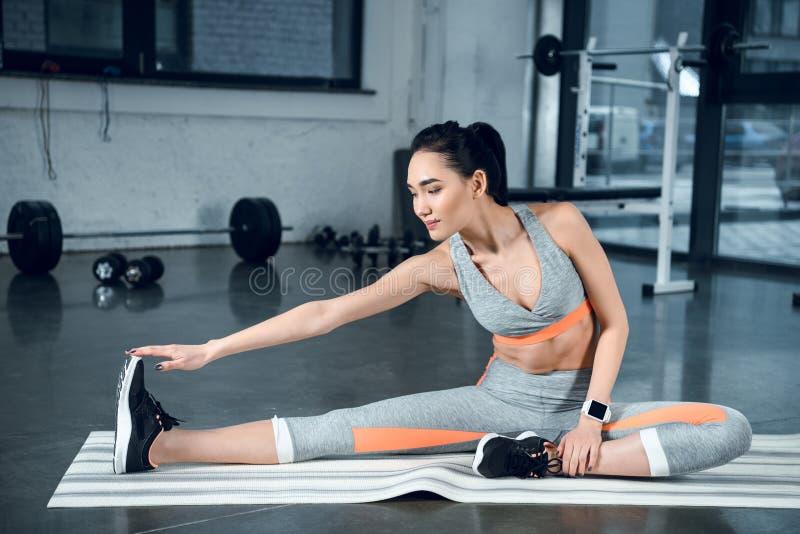 mulher atlética nova que faz a curvatura lateral na esteira da ioga foto de stock