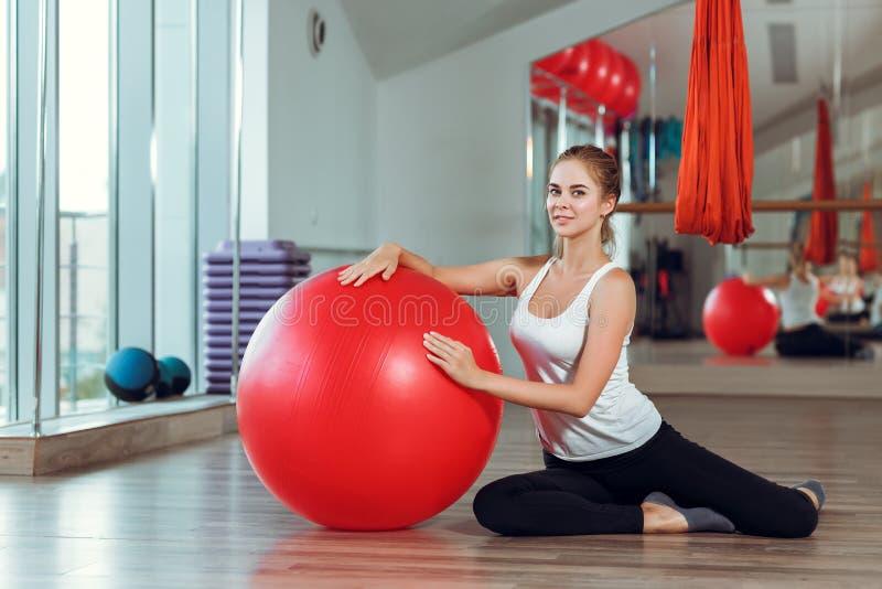 Mulher atlética nova que faz exercícios com a bola da aptidão no gym imagem de stock royalty free