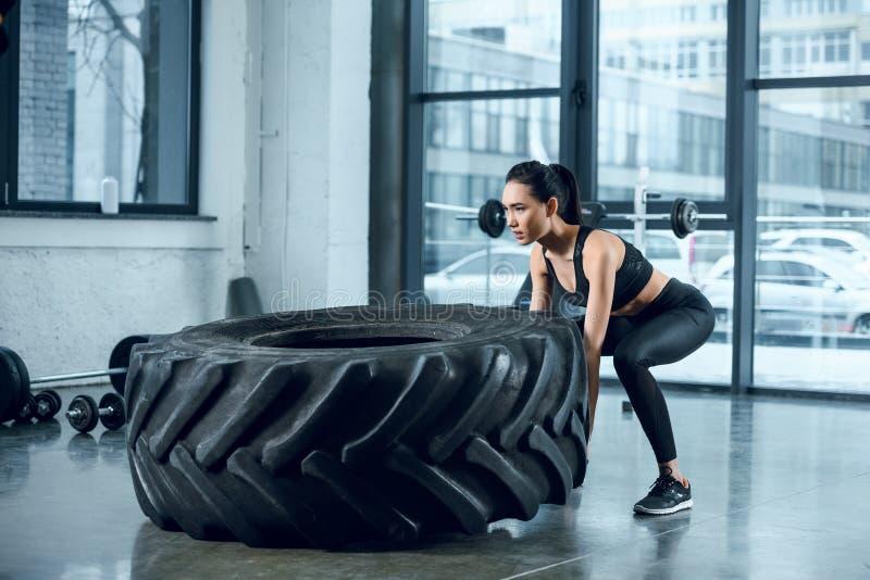mulher atlética nova que lança a roda do exercício fotos de stock